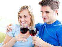富感情的夫妇饮用的沙发酒 免版税图库摄影