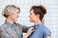 富感情的年轻女同性恋的看彼此的夫妇常设外部 免版税库存照片