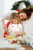 富感情的母亲在厨房帮助她的dughter搅拌在碗的鸡蛋,一起站立,烘烤所有的可口饼 免版税库存图片