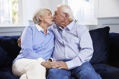 富感情的资深夫妇在家坐沙发 免版税图库摄影