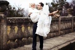 富有修饰,并且新娘huggingoutdoor背景墙壁草温暖a 库存图片