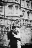 富有修饰,并且新娘huggingoutdoor背景墙壁草温暖a 免版税图库摄影