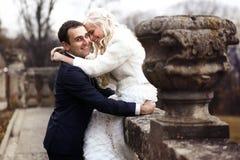 富有修饰,并且新娘huggingoutdoor背景墙壁草温暖a 免版税库存图片