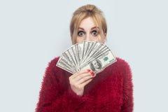 富有的可爱的年轻成人女实业家和现金美元的显示爱好者画象红色女衬衫身分的与大疯狂的眼睛的 免版税库存图片