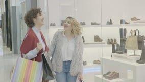 富有的姐妹为购物在购物中心得到激动,当他们看见完善的婚礼鞋子-时 影视素材