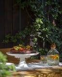 富有的巧克力蛋糕用草莓和可食的花在庭院-夏天心情里 免版税图库摄影