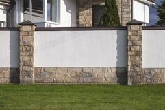 富有的房子、白色墙壁、水平的长方形石头和绿色草坪 库存图片