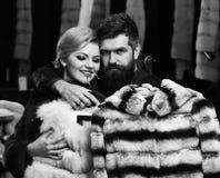 富有的时尚 有胡子的顾客和妇女买毛茸的外套 免版税库存图片
