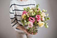 富有的束桃红色南北美洲香草和玫瑰开花,绿色叶子手中新鲜的春天花束 夏天背景 免版税库存图片