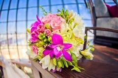 富有的束桃红色牡丹和淡紫色南北美洲香草玫瑰在窗口里开花,绿色叶子 新鲜的春天花束 免版税库存图片