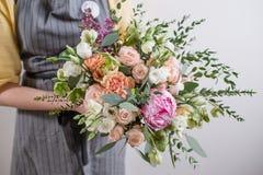 富有的束桃红色牡丹和白色南北美洲香草玫瑰开花,在玻璃花瓶的绿色叶子 新鲜的春天花束 夏天 免版税库存图片