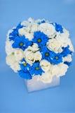 富有的束白玫瑰和蓝色花在玻璃花瓶 库存图片