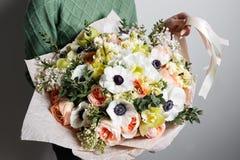 富有的束银莲花属、鸦片、丁香和白色兰花,绿色叶子手中新鲜的春天花束 夏天背景 库存图片