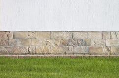 富有的白色墙壁、水平的长方形石头和绿色草坪 库存图片
