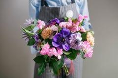 富有的花,绿色叶子手中新鲜的春天花束 夏天背景 免版税库存照片