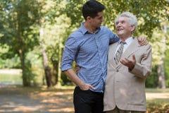 富有的年长男性和护工 库存照片