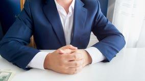 富裕的成功的商人的特写镜头图象在坐用被折叠的手的蓝色衣服的在现代办公室 免版税库存照片
