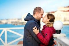 寒假、爱、浪漫史和人概念-拥抱愉快的微笑的年轻的夫妇户外 库存照片