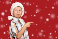 寒假圣诞节概念-圣诞老人帽子点的男孩他的fi 免版税库存图片