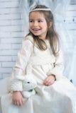 寒假礼服的女孩用玩具兔子 免版税库存图片
