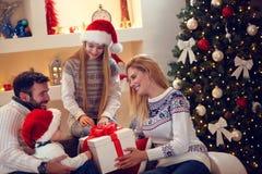 寒假-享用在圣诞节礼物的家庭 免版税库存图片