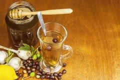 寒冷和流感的传统家庭治疗 野玫瑰果茶、大蒜、蜂蜜和柑橘 库存图片