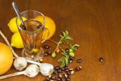 寒冷和流感的传统家庭治疗 野玫瑰果茶、大蒜、蜂蜜和柑橘 免版税库存图片