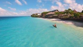 贫寒渔夫的鸟瞰图在沿一个热带海滩的一条小船航行 影视素材