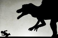 察觉追逐赛跑人的spinosaurus玩具的轻的投射阴影 免版税库存图片