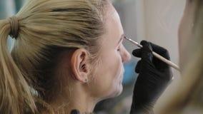 对一个俏丽的女孩的化妆师图画眼眉有在一个镜子前面的一把专业刷子的在美容院 影视素材