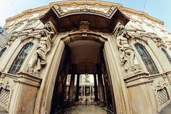 对一个历史建筑的曲拱的入口与雕塑的在边的其中一条意大利的街道 免版税库存照片
