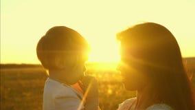 对一个小女儿的妈妈谈话 孩子在母亲的胳膊坐 幸福家庭在公园在春天走 股票录像