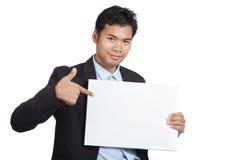 对一个空白的标志的亚洲商人点 免版税库存照片