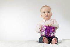 对一些负的严肃的男婴当前在他的胳膊 与礼物的周道的婴儿孩子 复制空间 准备好明信片 库存照片