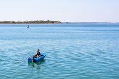 对一位渔夫的白天视图准备钓鱼竿的蓝色小船的 库存照片