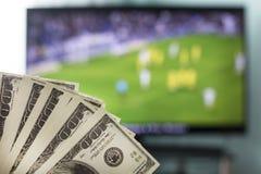 对一台电视机的背景的美元橄榄球、橄榄球和金钱的 库存照片