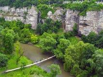 对一座巨大的山,从高度的一张照片的一座桥梁:一道岩石峡谷,在河下,一座稀薄的桥梁被舒展在拖曳 免版税库存图片