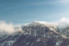紧贴对一座积雪覆盖的山的白色云彩 免版税图库摄影