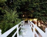 对一条人行道的白色桥梁在树 免版税图库摄影