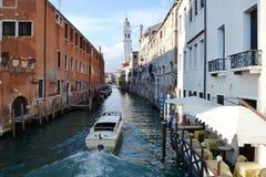 对一条运河的看法在有餐馆和汽艇移动的威尼斯 免版税图库摄影