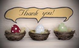 对三个五颜六色的复活节彩蛋的聚光灯与可笑的演说序幕感谢您 免版税库存图片