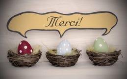 对三个五颜六色的复活节彩蛋的聚光灯与可笑的演说序幕Merci手段感谢您 免版税图库摄影