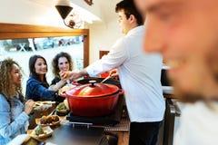 对三个俏丽的女孩的年轻厨师服务丸子食物卡车的 库存图片