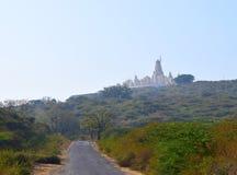 对上帝的方式-在小山和路的一个耆那教的寺庙- Hastagiri,印度 库存照片