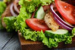 对与鸡和菜的新鲜的水多的套三明治 免版税库存照片
