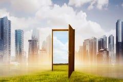 对与绿色草甸的新的世界打开木门 免版税库存图片