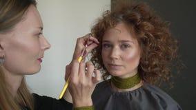对专业化妆师的特写镜头视图申请红色嘴唇光泽于模型 影视素材