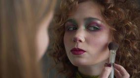 对专业化妆师的特写镜头视图申请红色嘴唇光泽于模型 股票视频