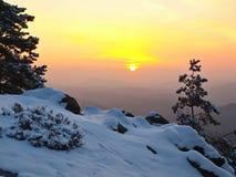 对东部的有风冬天早晨视图与橙色日出。在岩石的破晓 库存图片