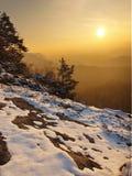 对东部的有风冬天早晨视图与橙色日出。在岩石的破晓 免版税图库摄影